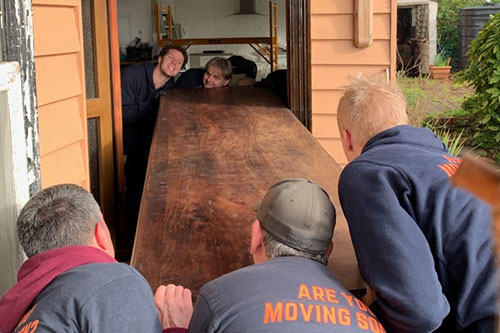 Removalists lifting heavy table through a door in Highton